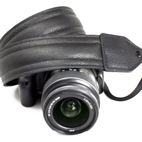 Black piped leather stitch camera strap.