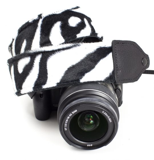 Black / white zebra faux fur camera strap.